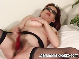 Mature redhead wearing unornamented but her shades and stockings plays with her aged pussy