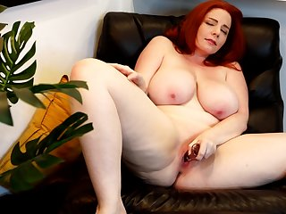 Insolent nude toying on a leather chair unconnected with a hot chubby redhead